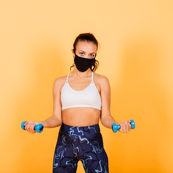 Quarantine is not a hindrance. dark-skinned sportswoman wearing a medical mask training with dumbbells. healthcare, fitness and quarantine concept.