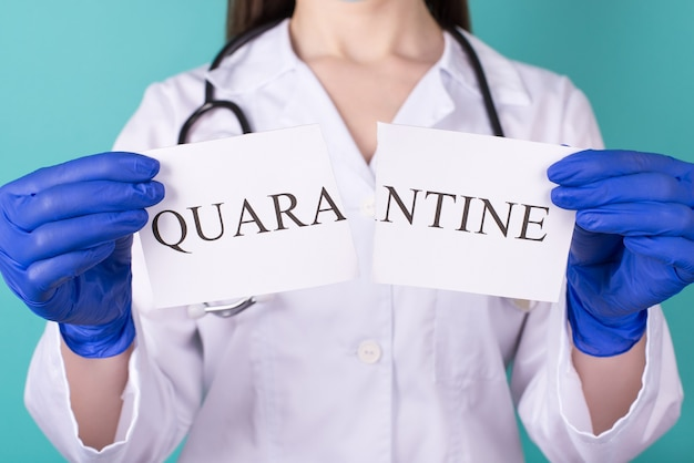 検疫は、自由な人々の自由の概念を超えています。青いティールの背景に分離された検疫紙の一部を保持している手袋をはめた女性医師のクローズアップトリミング写真