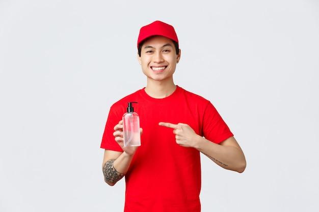 Карантин, безопасная бесконтактная доставка и концепция покупок в интернете. улыбающийся азиатский курьер в красной кепке и футболке объяснил необходимость использования дезинфицирующего средства для рук для предотвращения распространения коронавируса