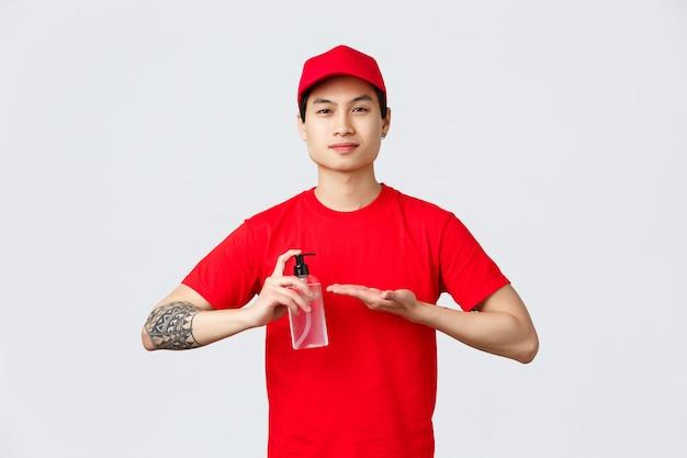 Карантин, безопасная бесконтактная доставка и концепция покупок в интернете. улыбающийся азиатский курьер в красной кепке и футболке наносит дезинфицирующее средство для рук на руки, чтобы предотвратить распространение covid-19 и вирусов.