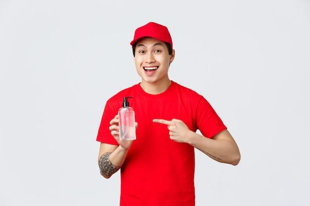 Карантин, безопасная бесконтактная доставка и концепция покупок. веселый улыбающийся азиатский курьер в красной кепке и футболке, указывая дезинфицирующее средство для рук, пропагандирует безопасные покупки, важность предотвращения распространения вируса