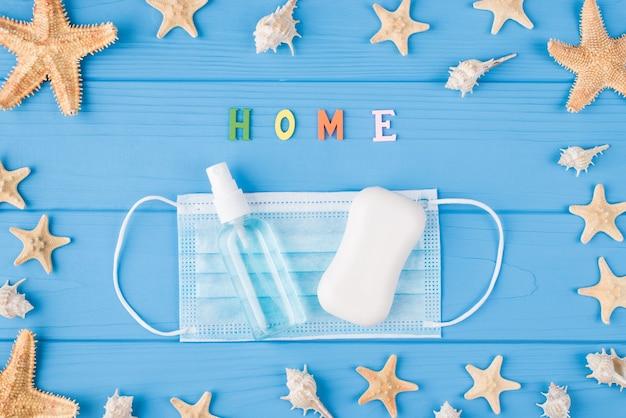 검역은 집 개념을 유지합니다. 파란색 생생한 배경에 있는 수술용 매스 소독 스프레이 흰색 바 비누의 오버헤드 클로즈업 보기 사진