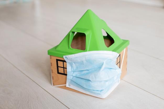 検疫外出禁止令コロノウイルスのコンセプト医療マスクのおもちゃの家が床に立っています