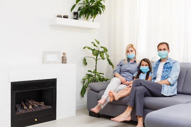 격리 시간: 거실에서 보호 마스크를 쓴 가족이 함께.