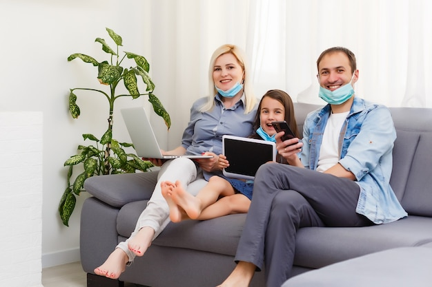 Quarantine time: family in protective masks at living room together.