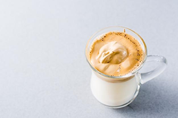 トレンディな料理を検疫します。灰色の背景にダルゴナコーヒーとカップ。
