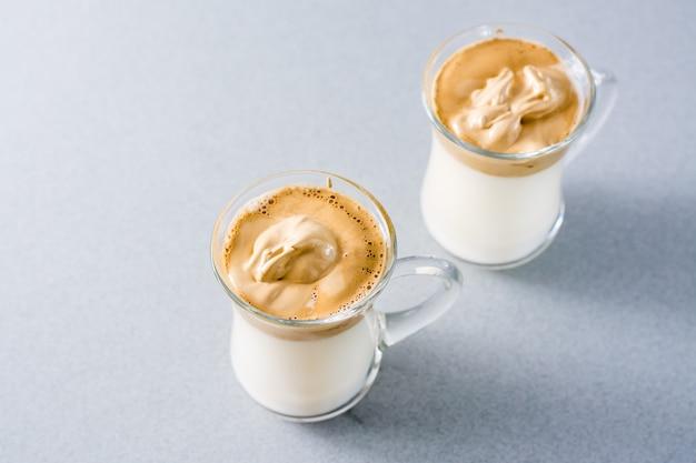トレンディな料理を検疫します。灰色の背景にダルゴナコーヒーと2つのカップ。