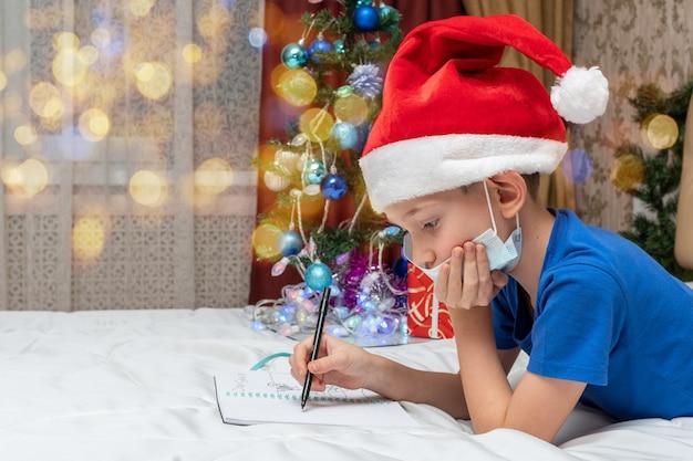 격리 크리스마스 개념. 의료 마스크와 빨간 모자를 쓴 어린 소년이 집에서 산타 클로스에게 편지를 씁니다.