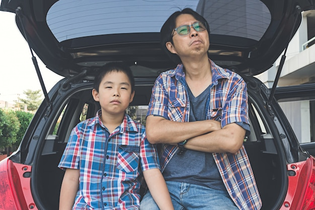 Quarrel of little son and father sitting in trunk of car