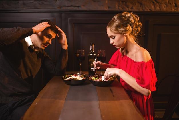 レストランでの若いカップルの喧嘩、こんばんは。赤いドレスを着たエレガントな女性とカフェで食べる彼女の男