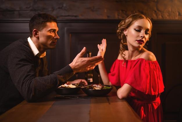 レストランでの若いカップルの喧嘩、悪い関係。赤いドレスと彼女の男がカフェで食べることでエレガントな女性