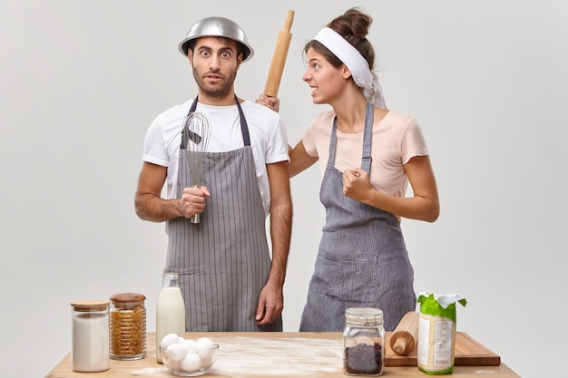 La moglie litigiosa tiene il mattarello di legno e stringe il pugno, guarda con rabbia il marito, lo fa aiutare a preparare la torta in cucina. marito e moglie pongono vicino al tavolo con stoviglie. tempo di cottura