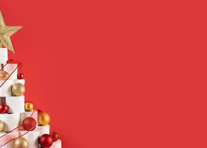 コピースペースの赤い背景の上のクリスマストイレットペーパーツリーの4分の1