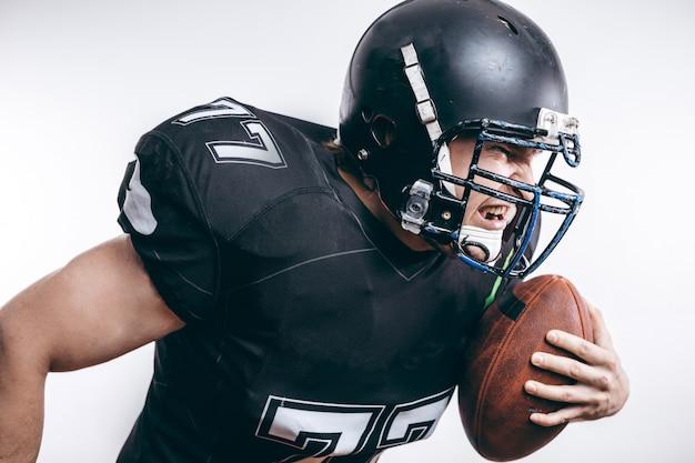 プロのフットボールの試合でフットボールを投げるクォーターバック