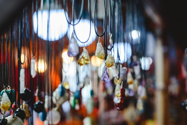 Quartz and other precious stones hung on necklaces in a mineral and beauty shop.