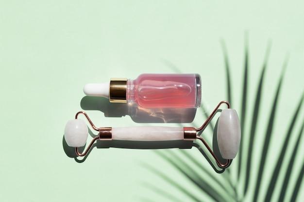 クォーツローラーとコメティック製品のボトル、青い背景にローズセラムまたはオイル。化粧品と道具。トレンディなハードライトのスキンケアコンセプト。