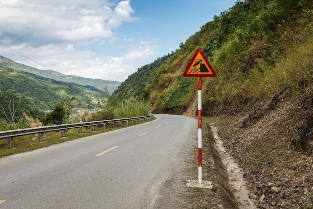 岸壁または川岸。ベトナムの山道の道路標識。