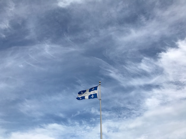 Quebec flag under the beautiful clouds in the sky