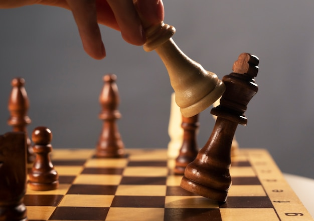 Queen beating king on chessboard