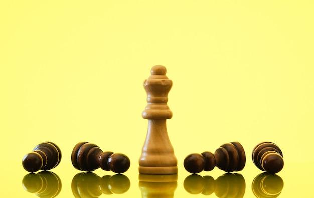 Королева побеждает черные пешки, современный желтый и серый фон. концепция силы, иммунитета и устойчивости.