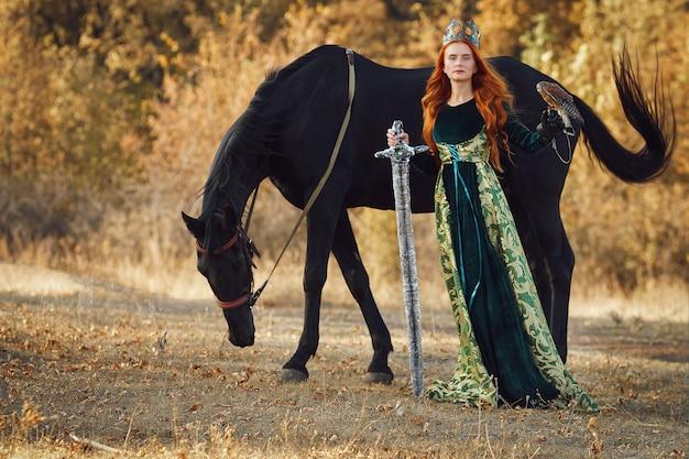 鳥と馬の近くに王冠と剣と緑のドレスを着た赤い髪の女王