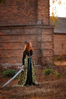 王冠と剣と緑のドレスを着た赤い髪の女王