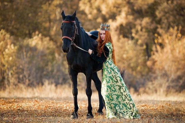 王冠と馬の近くの緑のドレスを着た赤い髪の女王