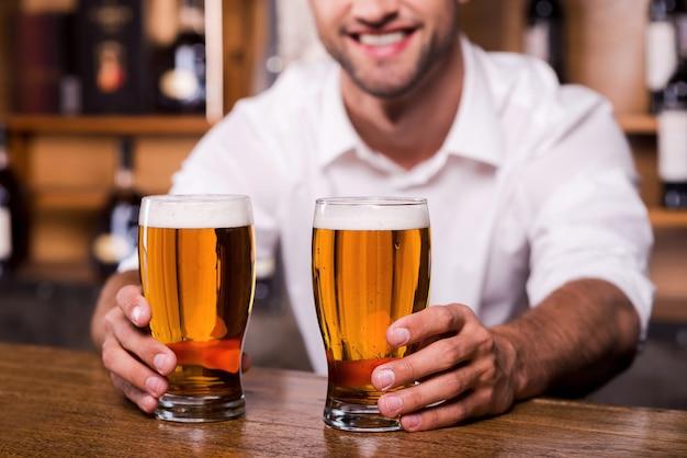 Утоли жажду! крупный план красивого молодого бармена-мужчины в белой рубашке, протягивающего бокалы с пивом и улыбающегося, стоя у барной стойки