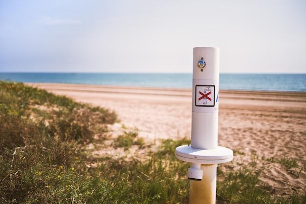 Quenoの警告サインが付いている浜辺にいる水浴者の足から砂を取り除くシャワーは飲料水です。