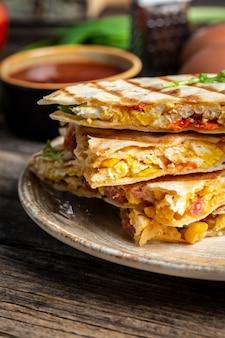 スクランブルエッグ、野菜、ハム、チーズを添えたケサディーヤの伝統的なメキシコのトルティーヤ