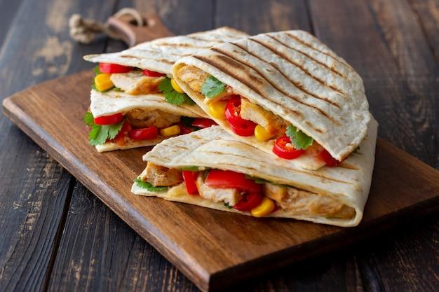 Кесадилья с курицей, помидорами, кукурузой, сыром и перцем чили. мексиканская еда. быстрое питание.