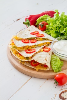 Quesadilla with sour cream, salad and tomatoes
