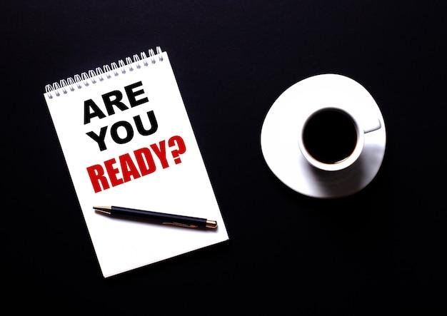 質問は、黒いテーブルの上の白い一杯のコーヒーの近くに、赤いタイプの白いノートに書く準備ができていますか。動機付けの概念