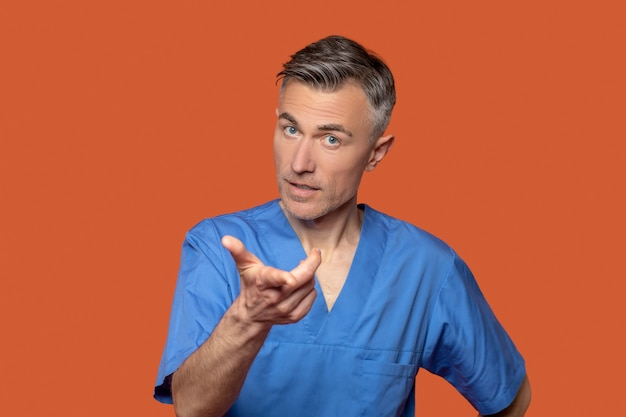 Question. friendly young adult man in blue suit with question gesture on orange background