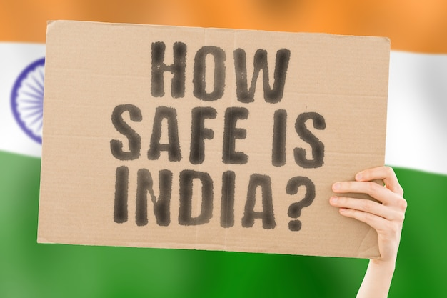 The question  how safe is india  on a banner in mens hand dangerous security attack criminal