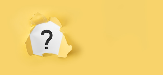 물음표 개념. 노란색 표면에 물음표와 함께 찢어진 된 노란색 종이.