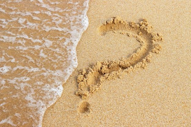 Вопросительный знак нарисован на золотом песке сверху, копия пространства
