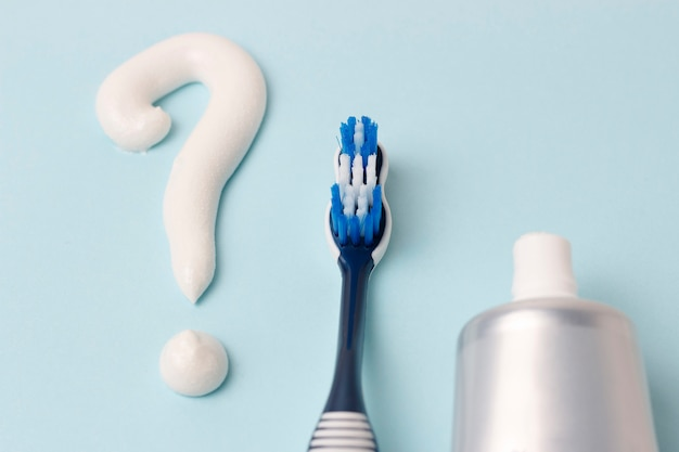 Question mark from toothpaste and toothbrush on blue background, choice concept
