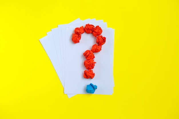 Question mark lined with crumpled paper on colorful  top view copy space