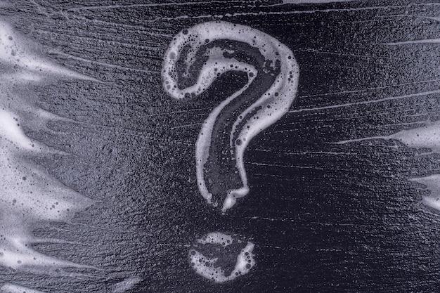 검정색 배경에 비누 거품으로 만든 물음표. 검은 배경에 추상 거품 텍스처입니다. 비누 거품 거품 추상 어두운 배경, 상위 뷰