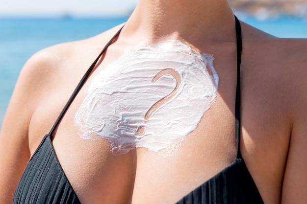 바다 배경 위에 여자의 가슴에 썬 크림으로 만든 물음표.