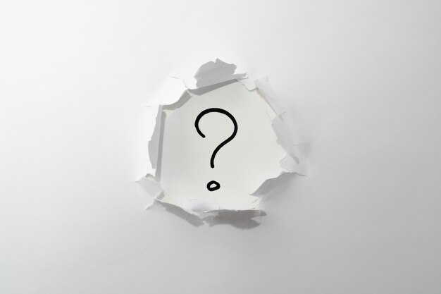 Вопросительный знак на белом фоне в отверстие бумаги.