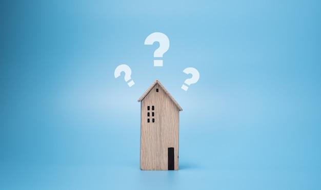 Вопросительный знак над деревянным домом. проблема, информация или faq
