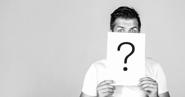 疑問符。問題と解決策。質問のシンボルの後ろをのぞく男の肖像画。疑問符、記号。物思いにふける男性。質問をします。疑わしい男が抱きしめている。スペースをコピーします。黒と白。