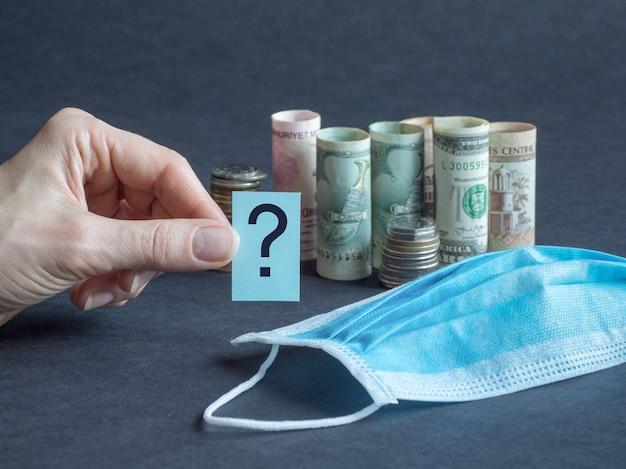 医療マスクとお金の疑問符。概念のパンデミックと経済危機