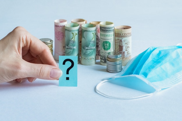 Question mark with medical mask and money. pandemic and the economic crisis of the concept