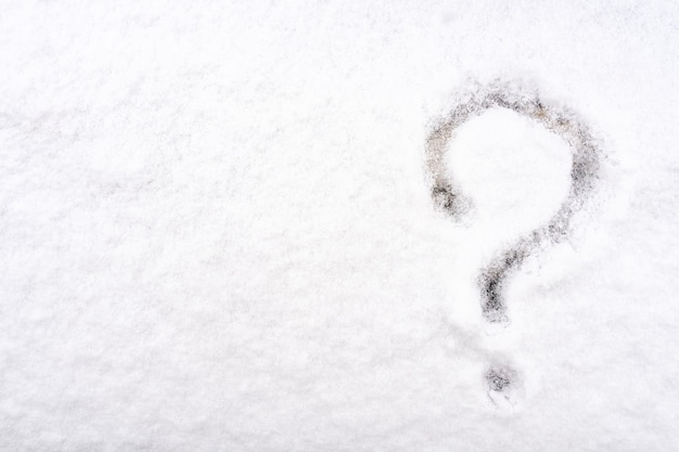 Вопросительный знак, написанный на свежем белом снегу в зимнее время