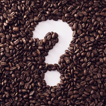 Question marked framed with roasted fresh coffee beans on a white background in square format