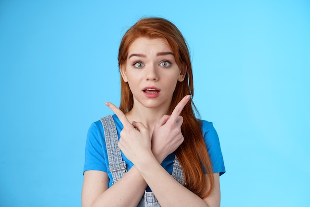 Questioned ambushed cute redhead woman asking advice picking product, cross hands pointing sideways, show left right choices, look camera wondered uncertain, making decision, blue background