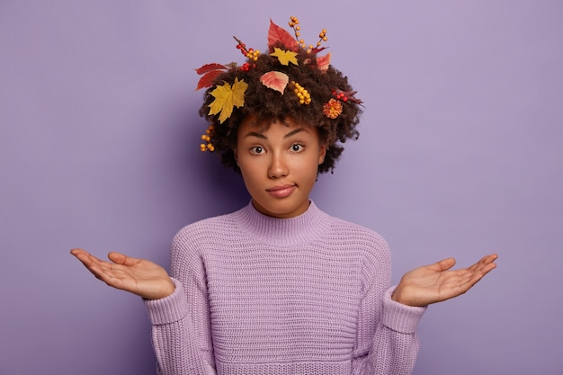Questioned clueless woman spreads palms, has autumnal ripe plants in haircut, wears knitted sweater, looks unaware at camera, isolated over purple background.
